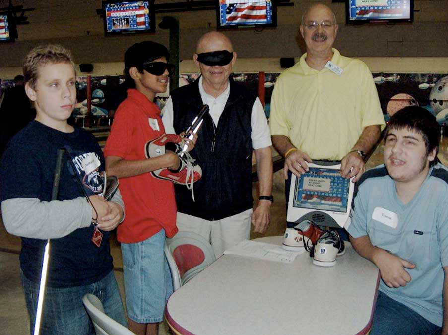 group picture of club members working at a school for the blind bowling night