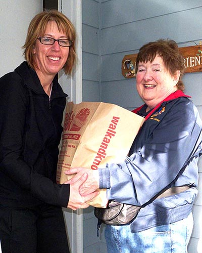 picture of Linda Bannon picking up food at walk and knock food drive